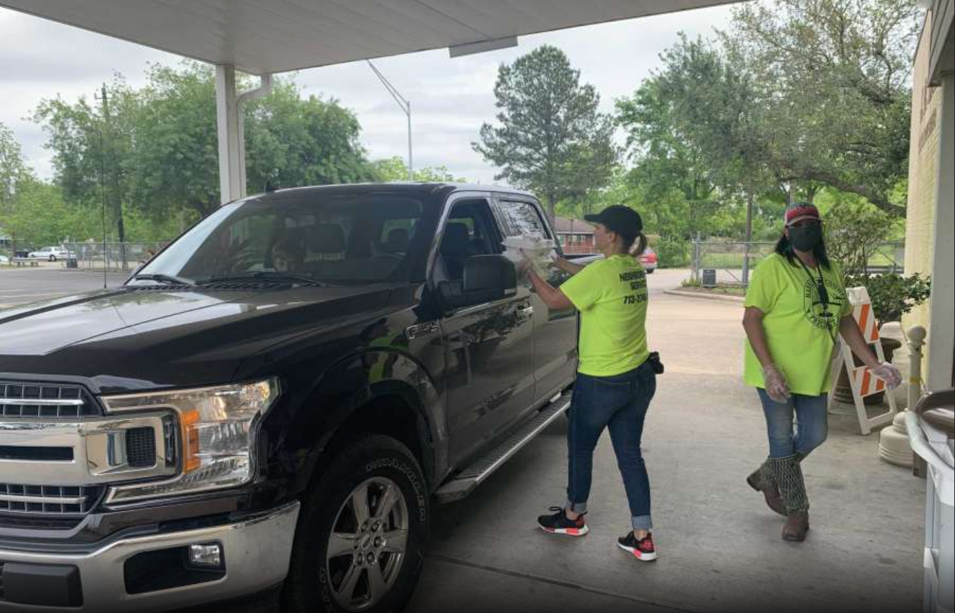 A Harris County staff member delivers containers of food to an individual in a black truck at a drive-thru food distribution centre.