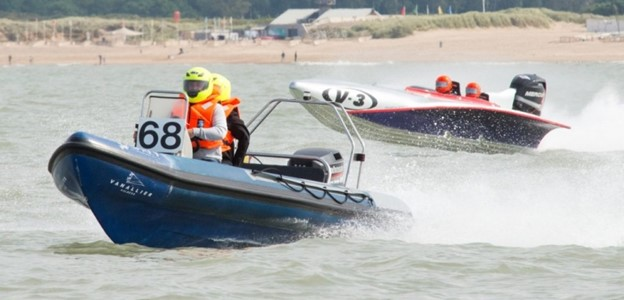A blue and silver boat each containing two team members race through the water.