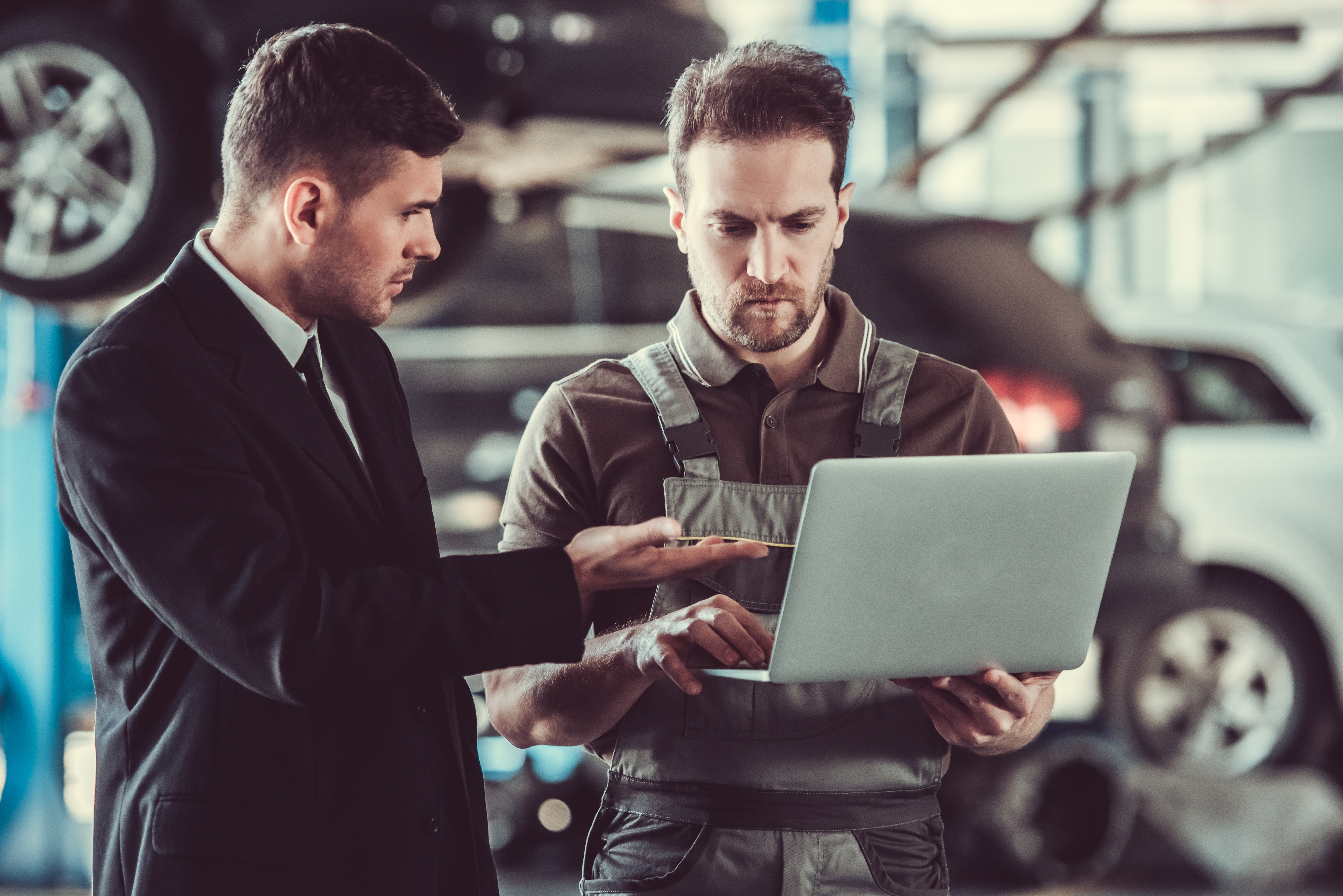 A man in a business suit is pointing to the laptop that is help by a worker in a jumpsuit.