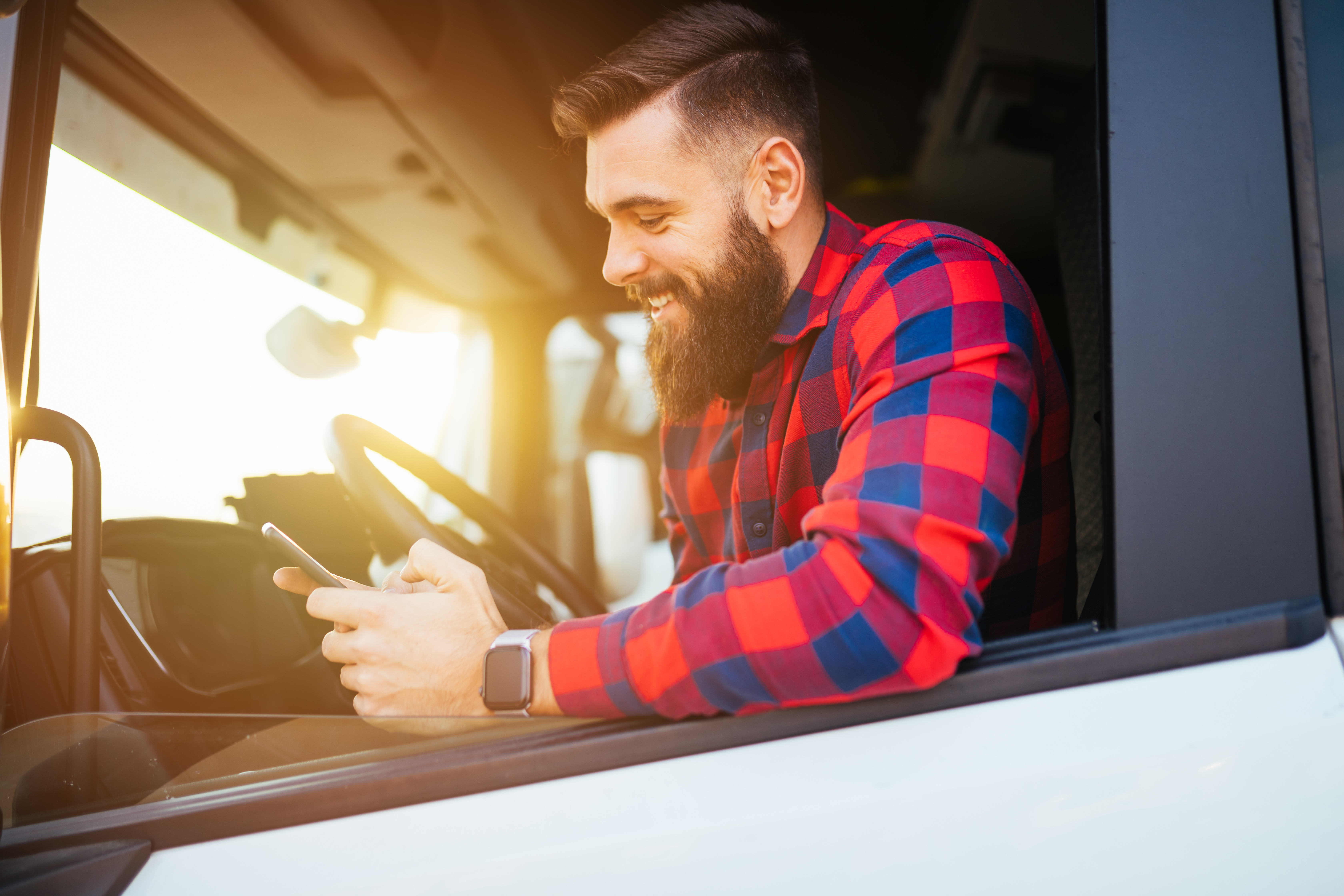 A man sitting at the driver seat of a truck smiles while looking at his smartphone screen.