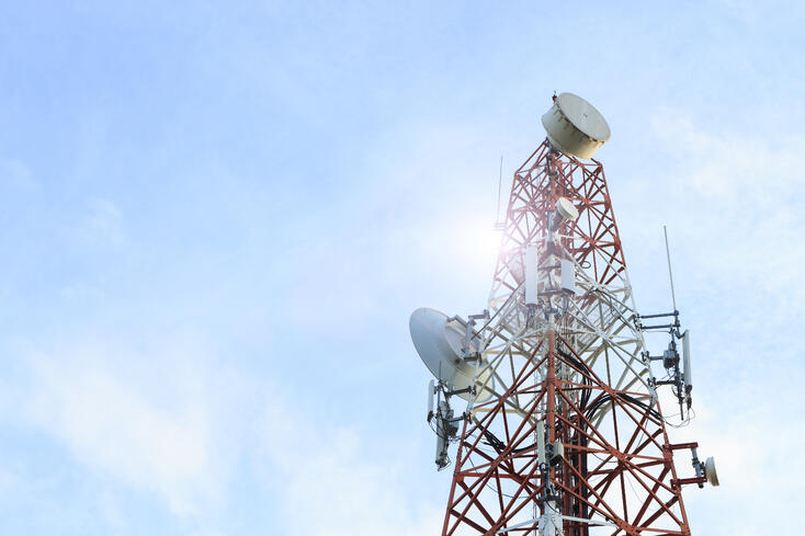 A telecommunications tower with the blue sky in the background.