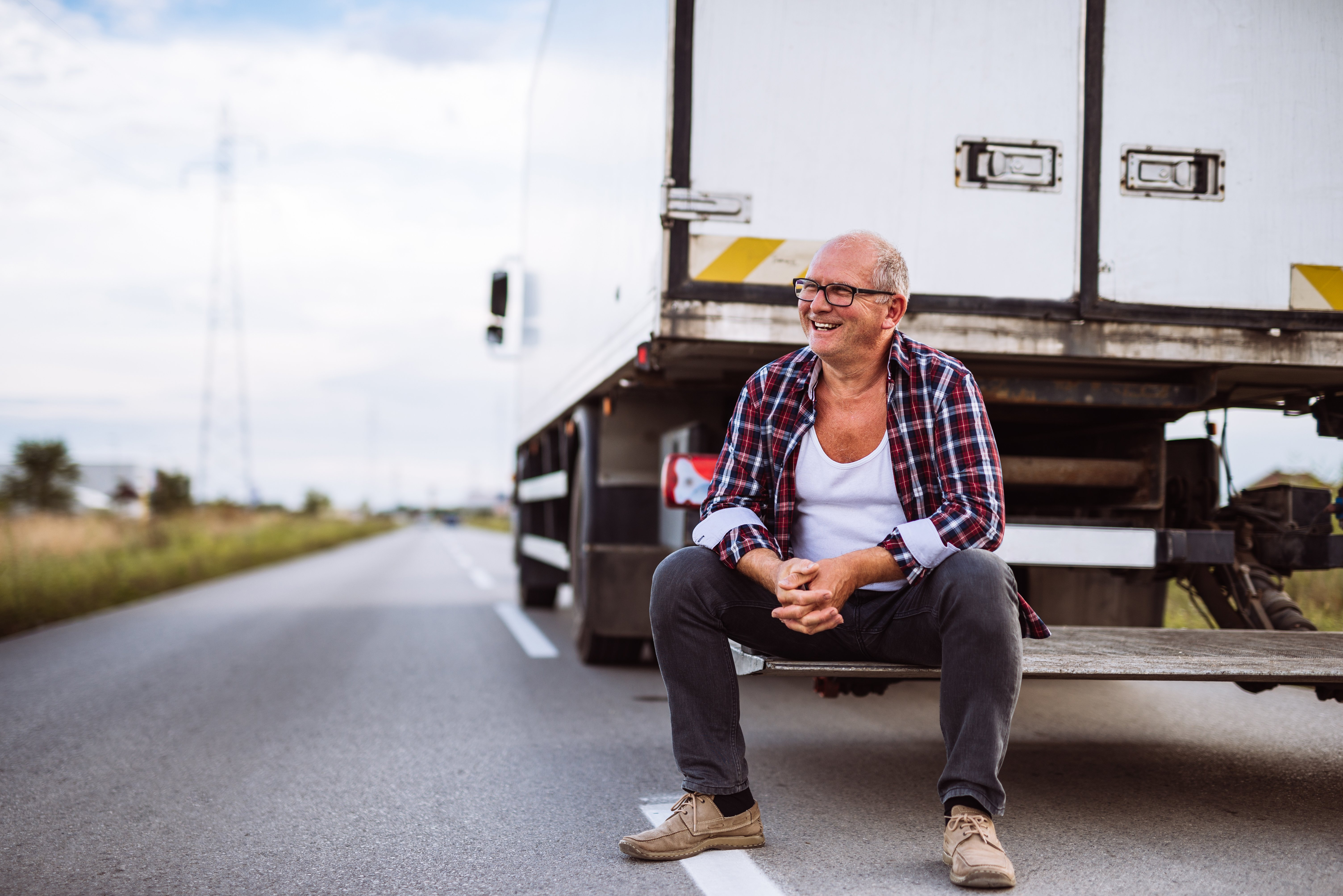 A truck driver sitting behind a white truck parked on the road, smiling.