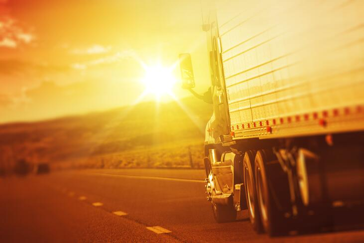 A truck driving down the road with the sun setting in the background.