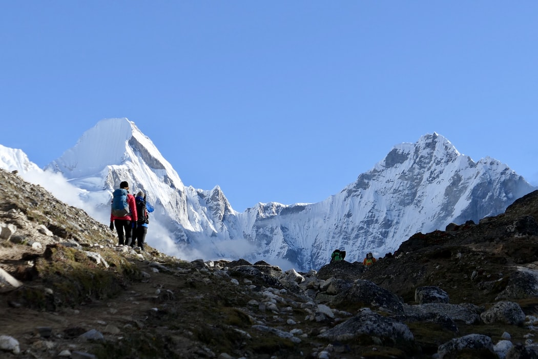 An outdoor landscape with Mount Everest in the background and hikers walking toward it in the foreground.