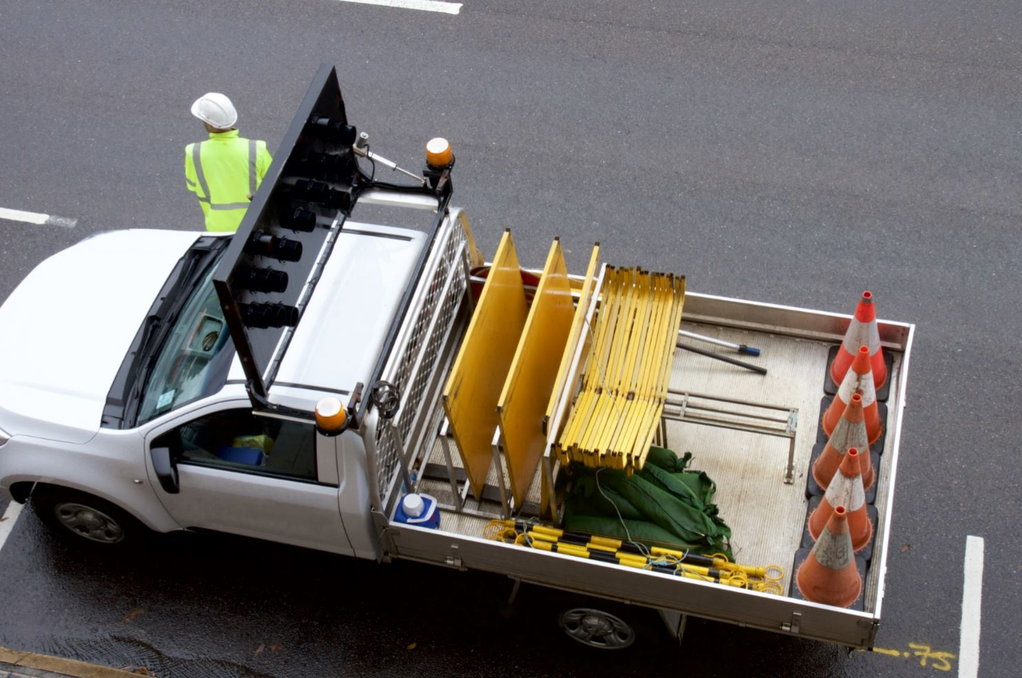 Arial view of a construction worker standing on the road next to the truck with traffic cones.