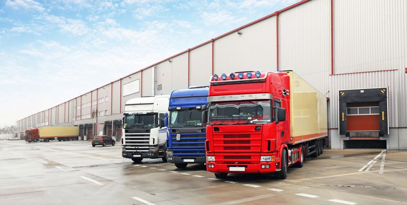 Trucks with IVMS tracking devices installed unloading at a warehouse.