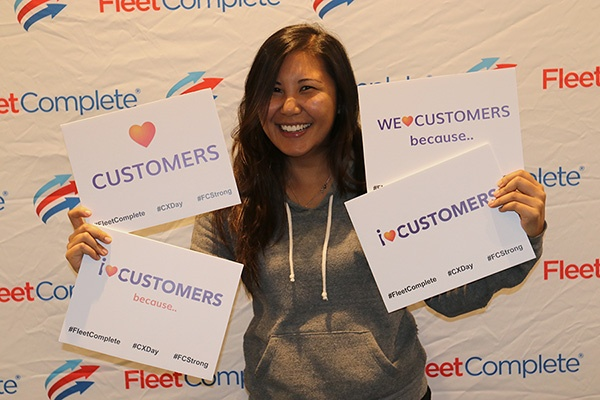 Eloisa holding cards that say we love customers.