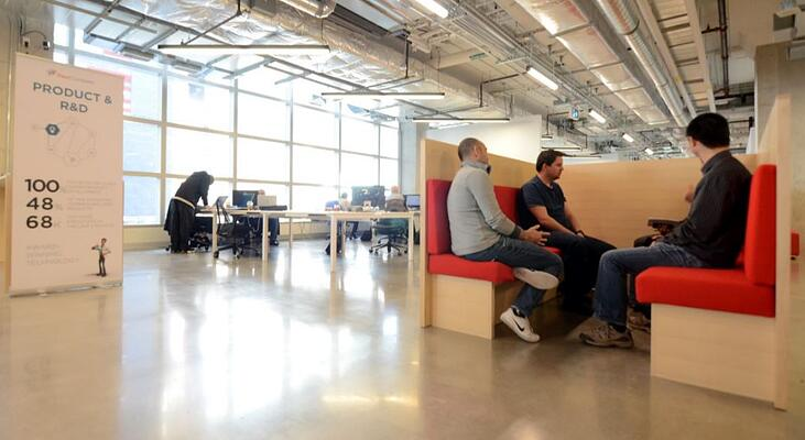 Fleet Complete office with product team having a discussion on red sofas.