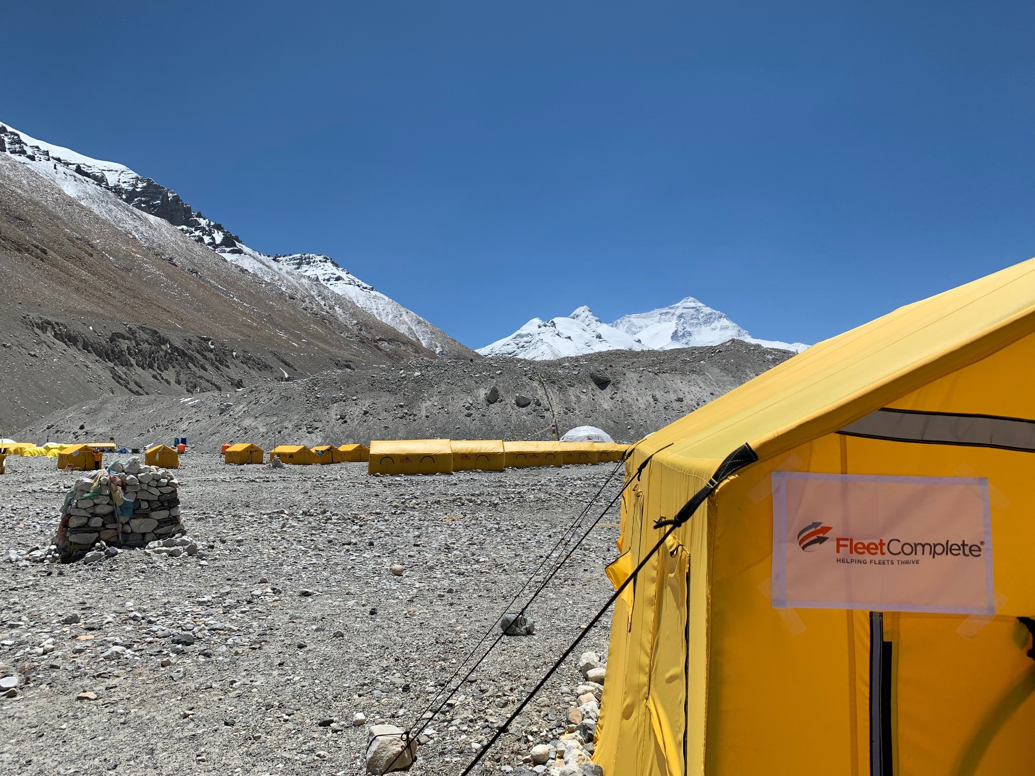 Base camp of Mount Everest with a tent and a Fleet Complete Logo display.