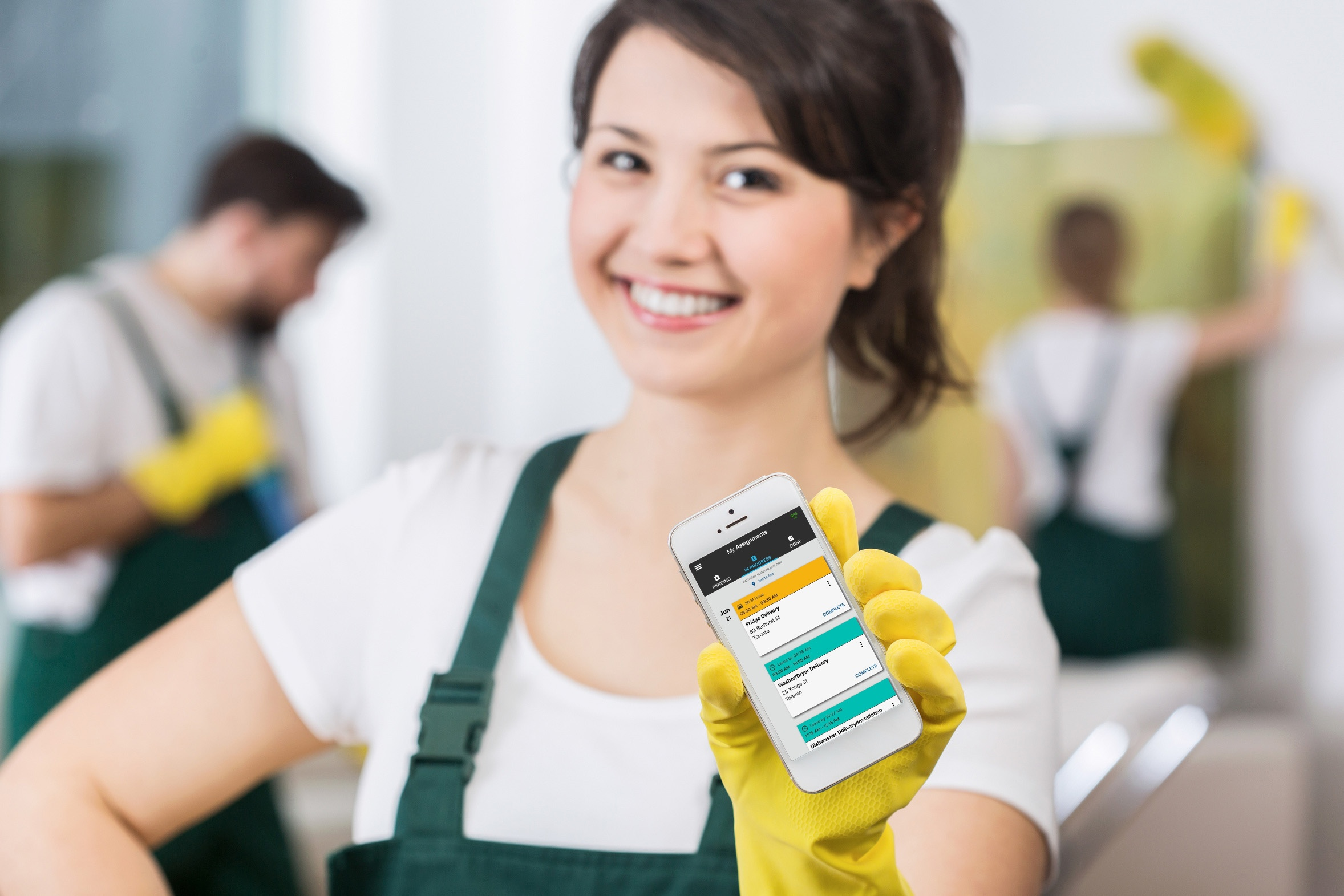 Young woman worker wearing yellow rubber gloves and holding a smartphone with Task Tracker app on the screen.