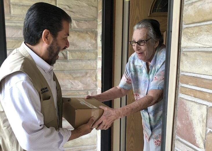 Harris County Precinct 2 Commissioner Garcia delivers a box of food to an elderly individual. (2)