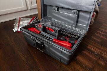 Small gray toolbox with red tools inside of it.