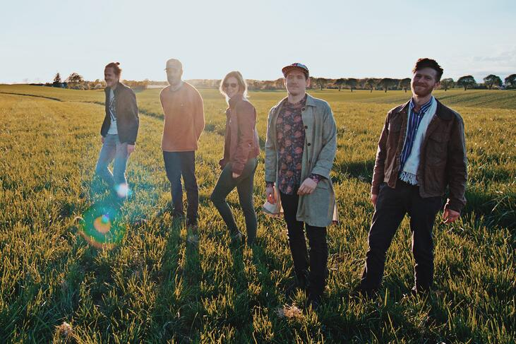 The five band members of Wild Forest stand in a grass field on a sunny day.