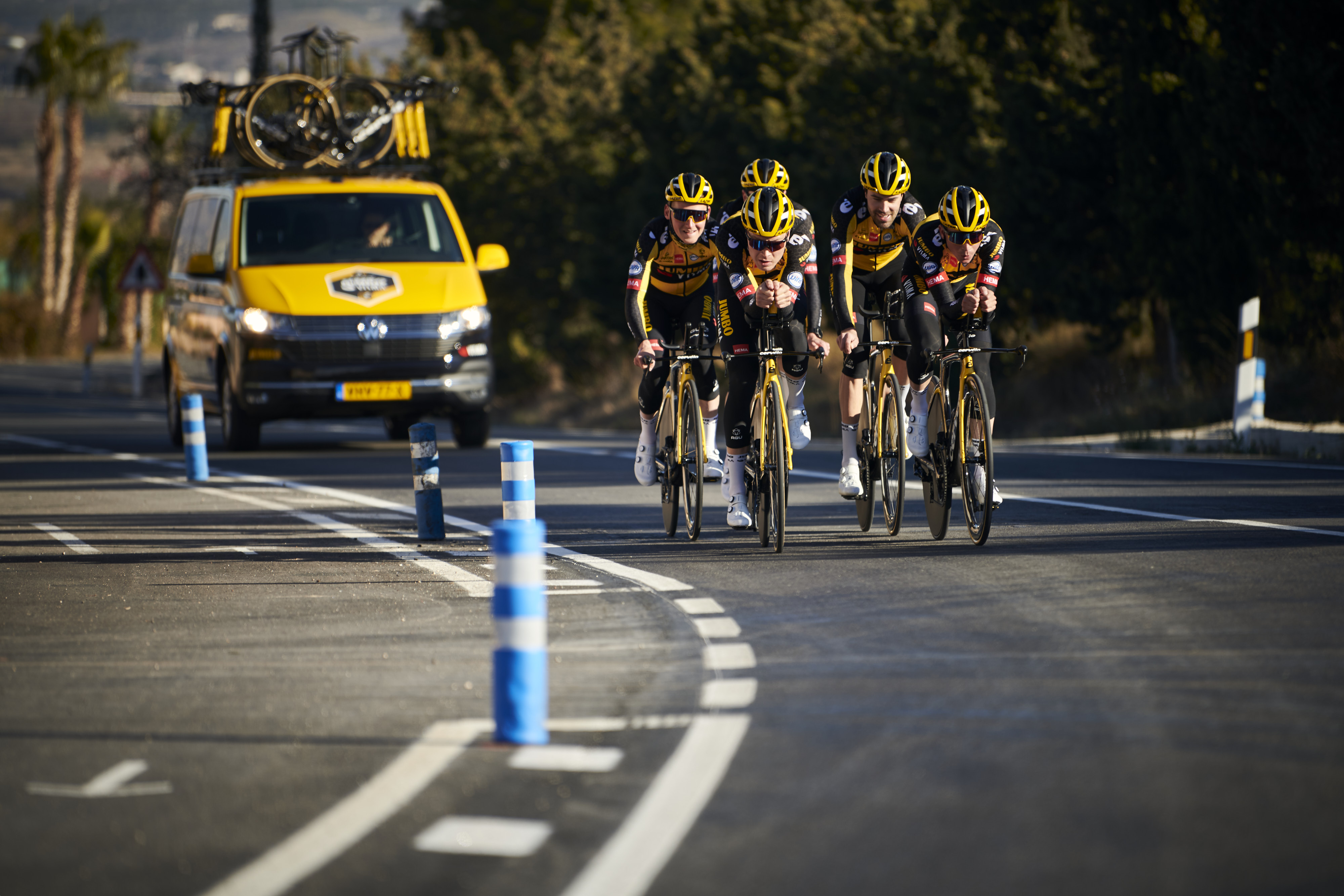 Training camp Alicante, five Team Jumbo-Visma pro cyclists on a track with a Skoda team van with spare bikes on top.