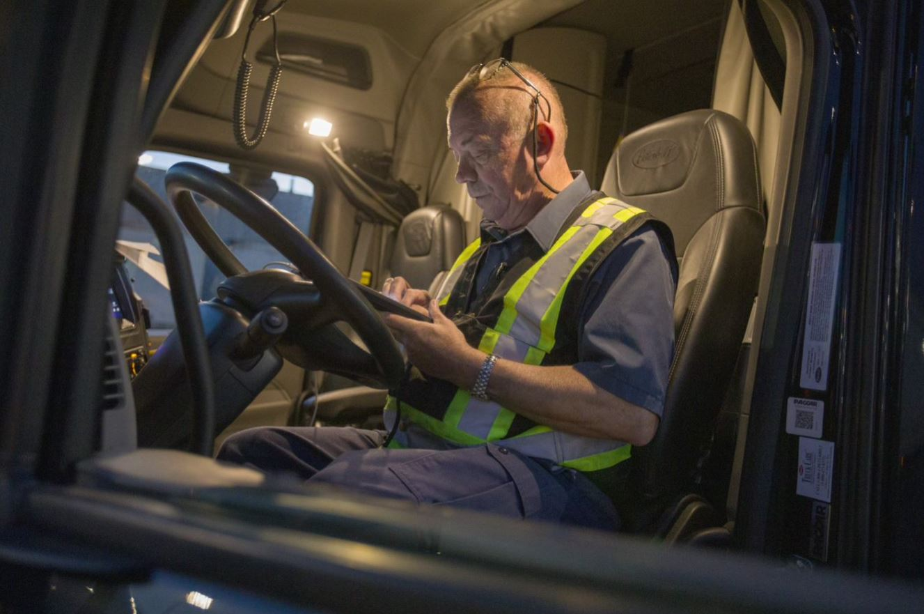 Truck driver looking at a mobile device inside truck cabin.