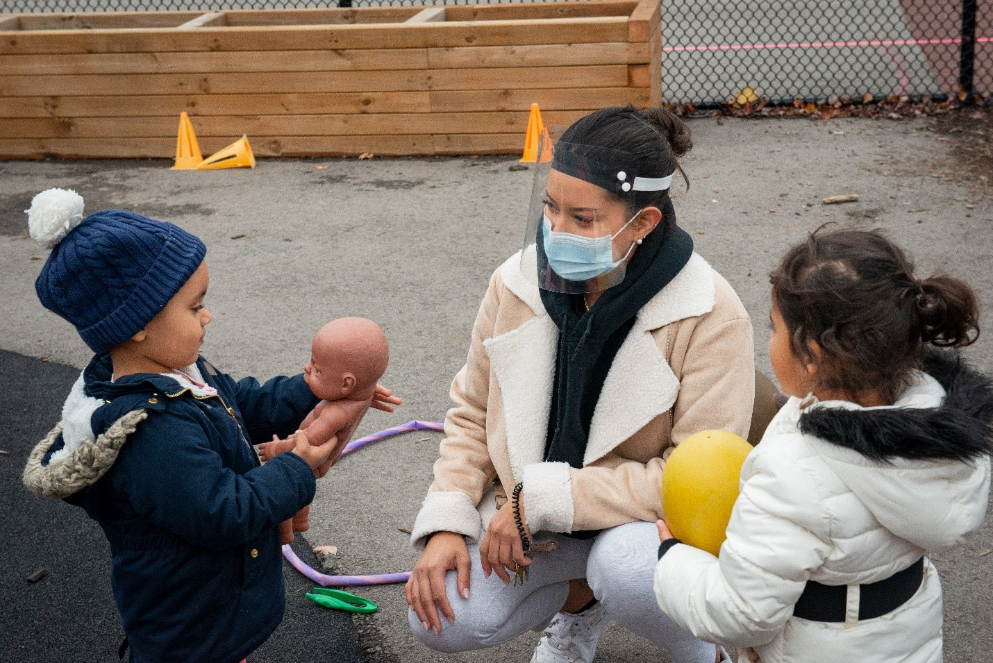 YMCA Child Care during COVID-19 a staff member wearing protective gear is outside during recess with 2 kids playing and smiling.