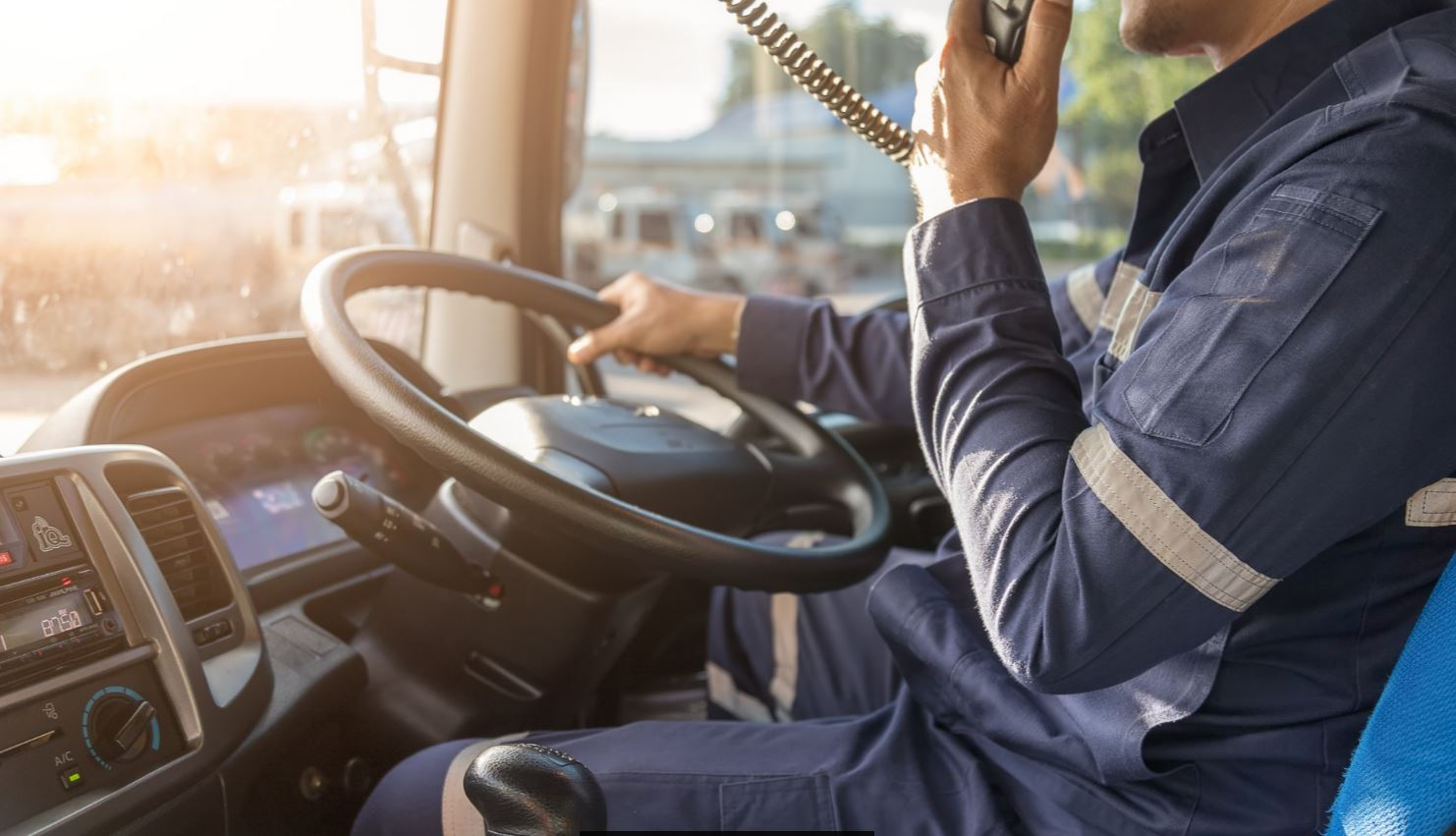 Driver at the steering wheel talking on radio dispatch.