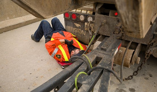 photo of worker carrying out preventative vehicle maintenance