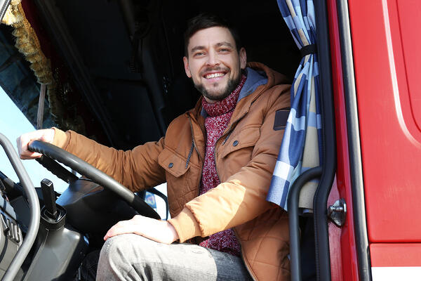 Smiling driver in a truck cab.