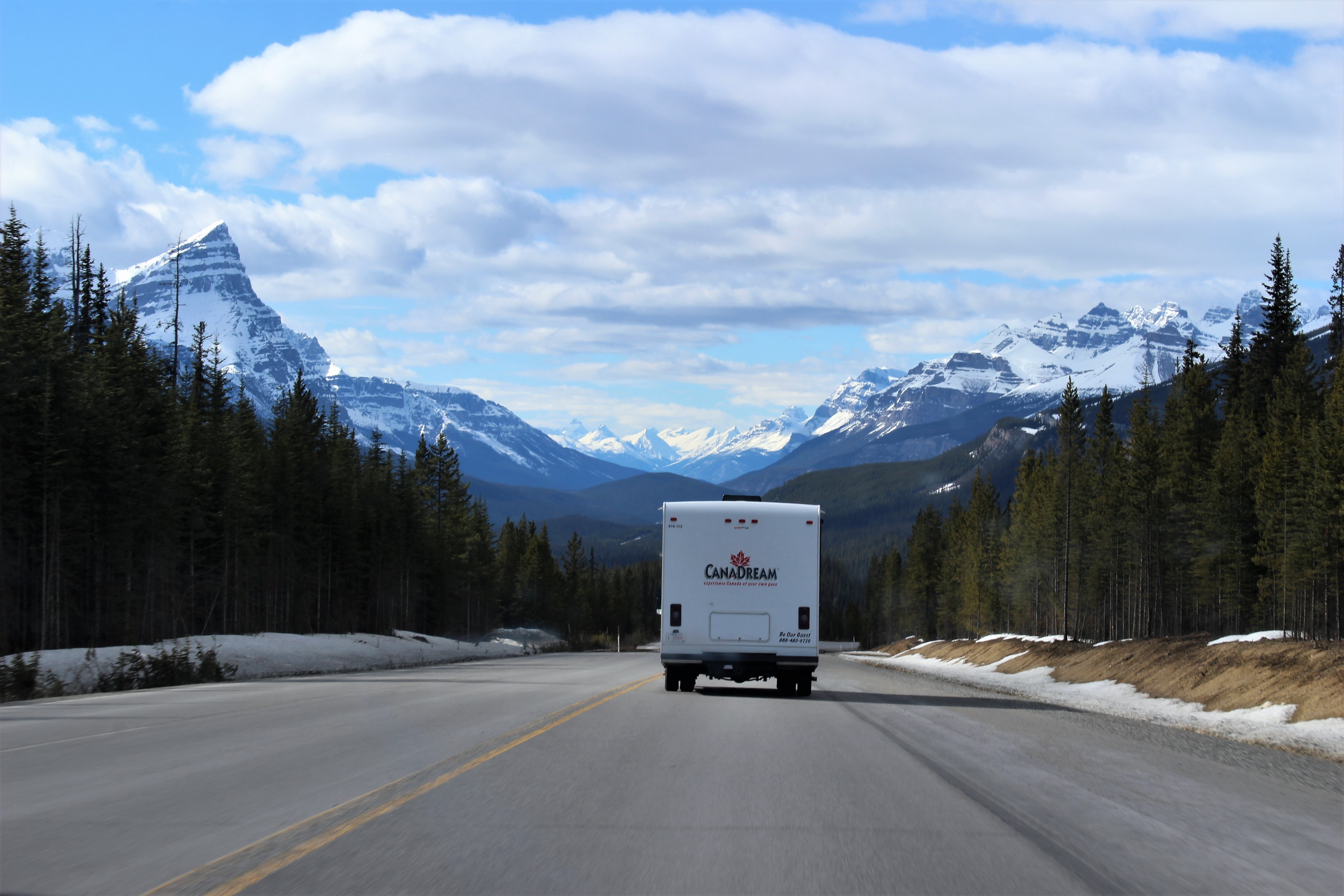 White CanaDream box truck on the road with mountains on background.
